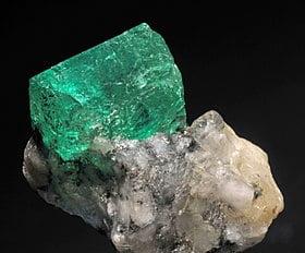 piedra de esmeralda en bruto dentro de otra piedra